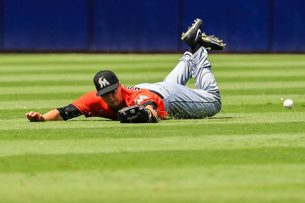Aug 11, 2013; Atlanta, GA, USA; Miami Marlins center fielder Jake Marisnick (23) is unable to catch a ball hit by Atlanta Braves starting pitcher Mike Minor (36) in the fifth inning at Turner Field. Mandatory Credit: Daniel Shirey-USA TODAY Sports ORG XMIT: USATSI-123810