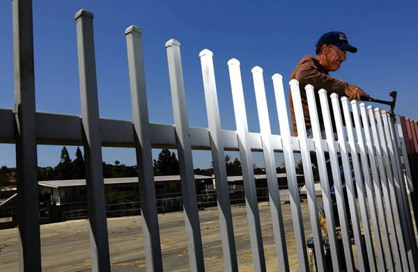 Vahe Takhman hammers on a nearly completeed fence surrounding Monterey Highland Elementary School in Monterey Park. Some students and residents have objected to the fence but Alhambra School District officials say they believe it will make the campus safer.