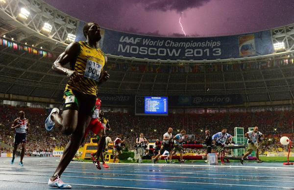 Lightning flashes as Jamaica's Usain Bolt wins the 100 meter final at the 2013 IAAF World Championships at the Luzhniki stadium in Moscow.