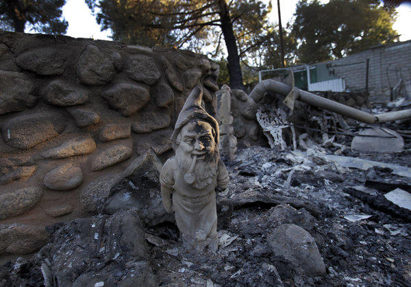 A gnome stands at the entrance of a burned-out home on Aug. 9 in the Poppet Flats neighborhood, after the Silver fire burned 26 homes and seriously injured one person.