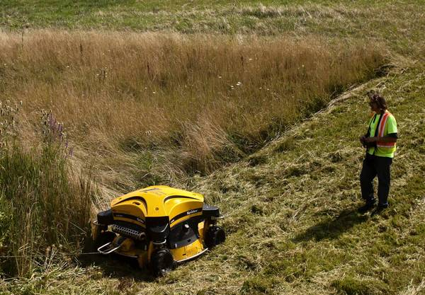 Illinois Tollway worker Paul Borkowski drives a Spider ILD02 remote-control lawnmower near Interstate 90 and the Tri-State Tollway intersection last week in Rosemont.