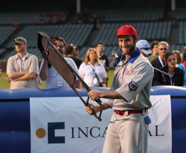 WWE Superstar CM Punk uses a chair while at bat during Woody's Wiffle Ball Classic at Wrigley Field Aug. 10, 2013.