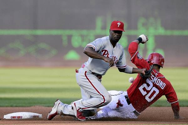 Ian Desmond of the Washington Nationals steals second base as Jimmy Rollins of the Philadelphia Phillies reaches for the throw in the fourth inning during a game at Nationals Park.
