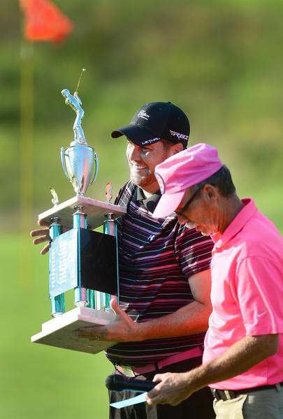 Gary Carpenter, of Crofton, Md., holds his championship trophy on the 18th green iafter winning the 2013 WACO Open title on Sunday at Beaver Creek. In front is tournament director Rod Steiner.