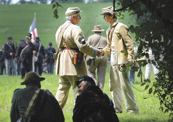 Two Confederate Civil War re-enactors shake hands after being defeated by their Union counterparts Sunday at Renfrew Park in Waynesboro, Pa.