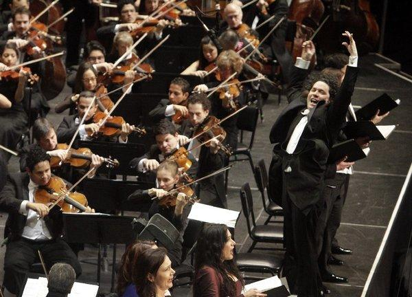 Gustavo Dudamel conducting members of the Los Angeles Philharmonic and the Simon Bolivar Symphony Orchestra in Mahler's Eighth Symphony at the Shrine Auditorium in 2012.