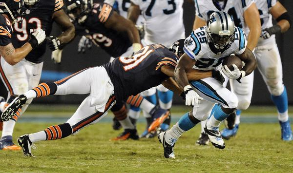 The Panthers' Kenjon Barner shakes off Isaiah Frey in the second quarter during preseason action.