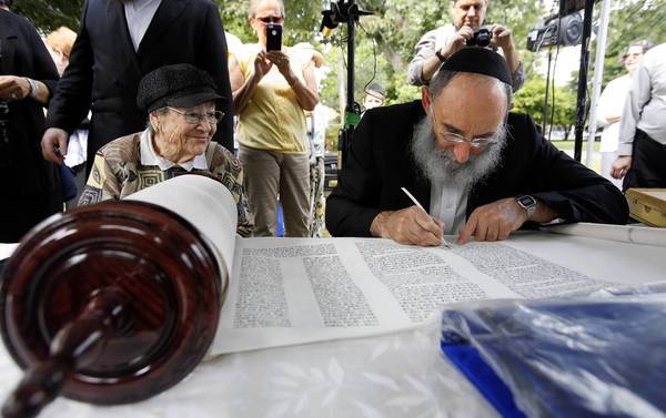 Holocaust survivor Marge Fettman, 88, of Lincolnwood, watches as scribe Yochanan Nathan fills in the last letters of the Torah she donated to the Lubavitch Chabad of Skokie.