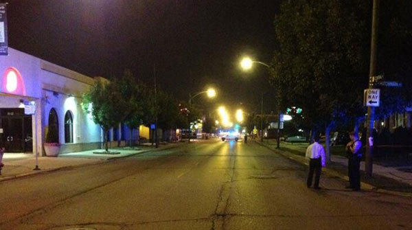 Police investigate the scene where three people were shot in the Portage Park neighborhood.