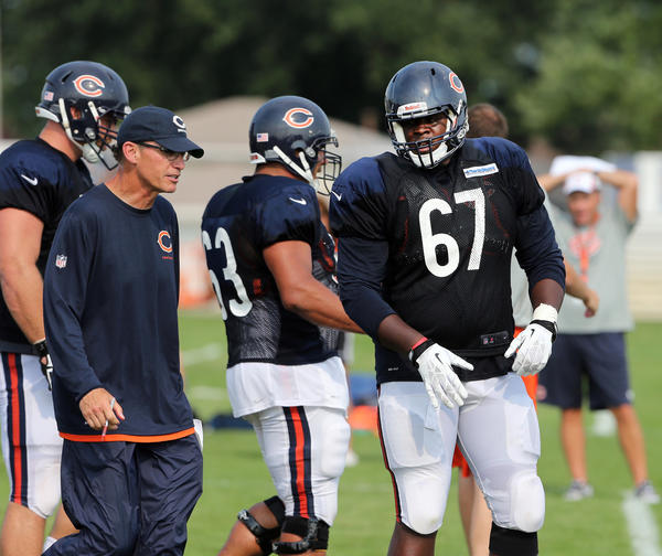 Bears head coach Marc Trestman instructs offensive tackle Jordan Mills (67) during their practice Sunday at Olivet Nazarene University.