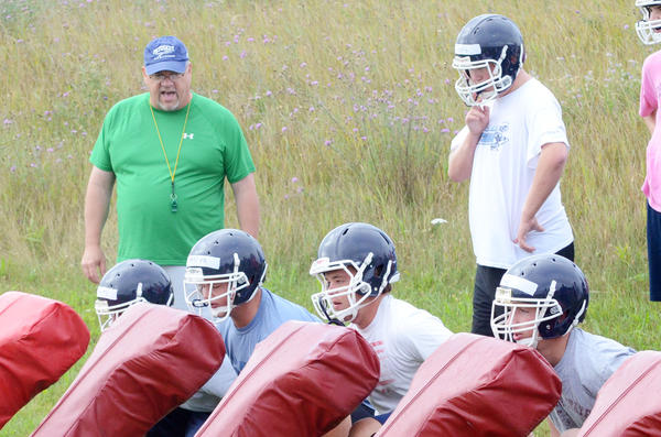 Veteran Petoskey High School varsity football coach Kerry VanOrman (left) shouts out instruction during the first day of practice Monday at the Petoskey High School athletic fields. Monday was the first day of practice for the Northmen as well as 600-plus other schools across the state. The Northmen will practice for three days without pads as mandated by the Michigan High School Athletic Association before the true hitting begins Thursday. The Northmen, who finished 5-4 last season, open the 2013 season on Aug. 30 at home against Sault Ste. Marie in a non-league contest at Curtis Field.