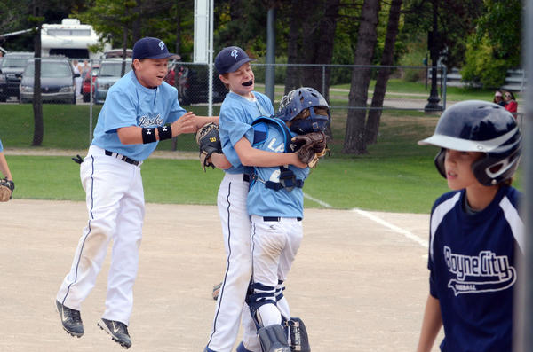 Petoskey 12U players including (from left) Nate Rodriguez, Nathan Spadafore and Timmy Lake celebrate moments following Spadafores strike out which gave Petoskey a 5-4 victory over Boyne City Sunday during a pool play game at the Sunset Showdown youth baseball tournament at Bayfront Parks Ed White Field. A total of 24 teams in age divisions 9U, 10U and 12U participated in the tournament, which took place at Bates Park and at Bayfront Parks Ed White Field.