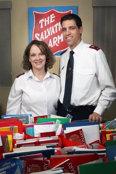 Newly named executive directors of the Salvation Army, lieutenants Jessica and Joshua Sheed, stand with back-to-school gift bags they and volunteers recently assembled at the Salvation Army in Glendale