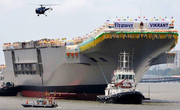 Tugboats guide the domestically built aircraft carrier INS Vikrant as it leaves the Cochin Shipyard after the launch ceremony in Kochi, India, on Monday.