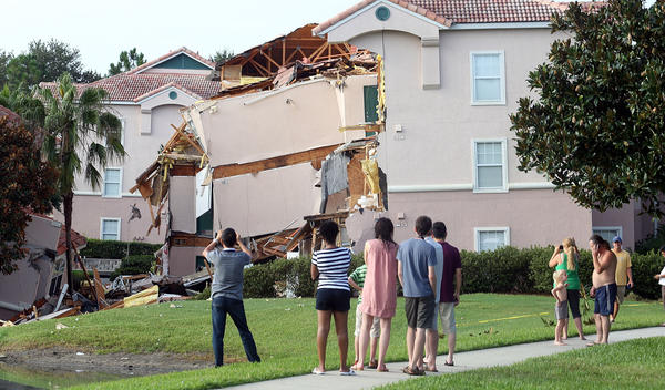 People inside the resort take pictures Monday after a sinkhole swallowed two building at Summer Bay Resort late Sunday night.