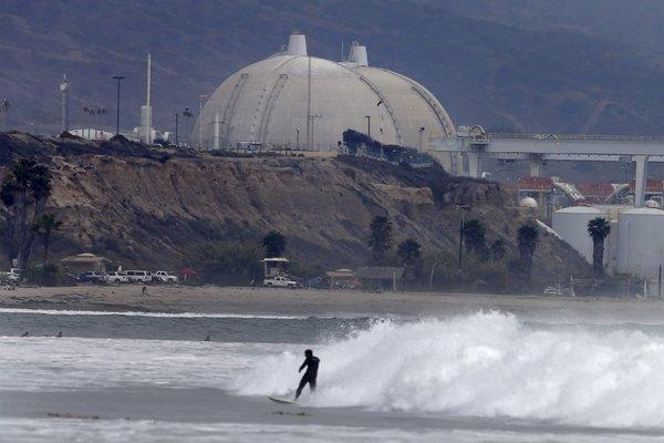 A surfer can be seen near the San Onofre Nuclear Generating Station. Southern California Edison is telling ratepayers that they must pay a portion of the costs to shut down the nuclear plant.