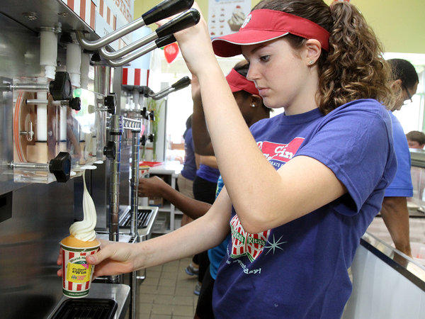 Sarah Terry, 16, of La Canada, fills an order at the grand opening of Rita's Italian Ice in La Canada Flintridge. This is Sarah's first job.