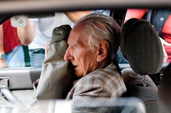 Alleged Hungarian war criminal Laszlo Csatary covers his face in a car as he leaves the Budapest prosecutor's office in 2012, where he was questioned by detectives on charges of war crimes. He was indicted in June 2013 by Hungarian authorities for abusing Jews and contributing to their deportation to Nazi death camps during World War II.