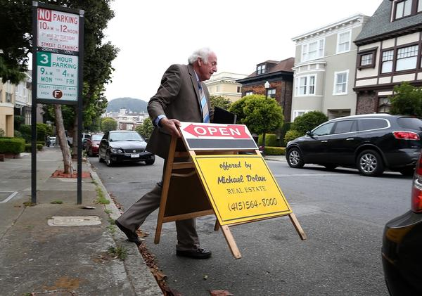 Demand for mortgages to purchase homes has increased as housing markets improve, although overall demand for home loans has declined as fewer homeowners find it worthwhile to refinance. Above, a real estate agent places an open-house sign in front of a home for sale in San Francisco last month.