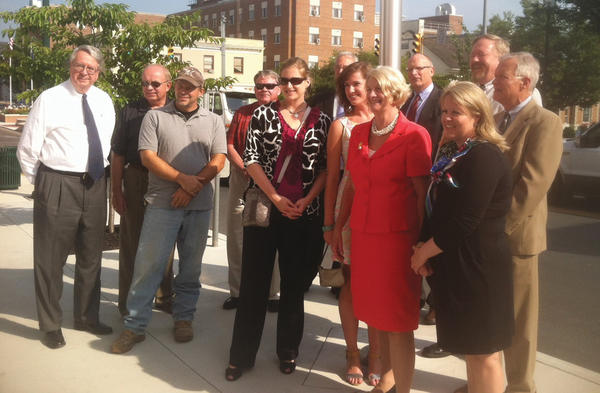 Former Del. Charlotte Lane of Kanawha County, wearing red dress, poses Monday with Berkeley County Republican party leaders and campaign supporters outside the Berkeley County Courthouse after announcing her bid for West Virginia's 2nd District seat in Congress.