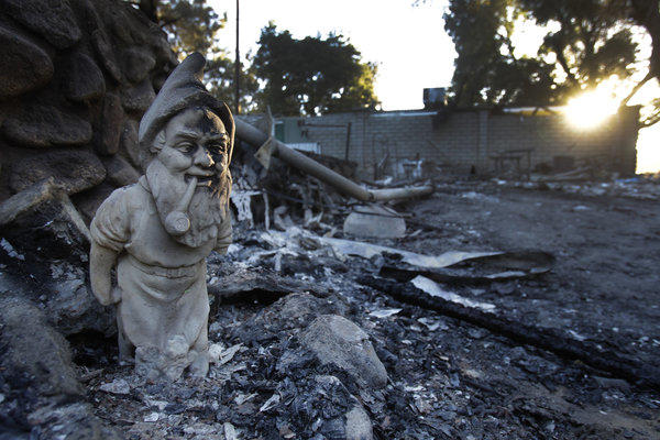 A yard gnome seems to stand sentry near a burned-out home in the Poppet Flats neighborhood after the Silver fire burned through.