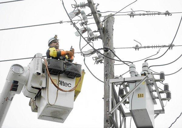 A utility worker helps restore power in Bethlehem, Pa., after a storm. The national power grid is increasingly vulnerable to outages from extreme weather, a federal report concludes.