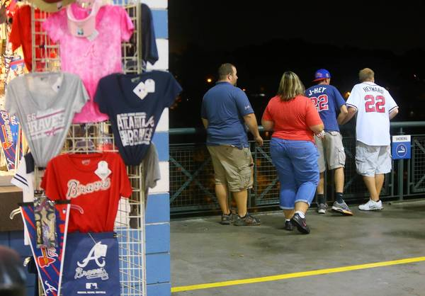 Baseball fans look over the railing of Turner Field at the scene where a fan apparently fell over an adjacent railing to the concrete several stories below next to the Braves players parking lot at their game against the Phillies on Monday.
