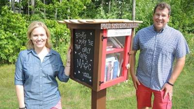 Loren (left) and Kevin VarnHagen stand near the Little Free Library they set up outside their home in the Chapel Hill subdivision near Petoskey.