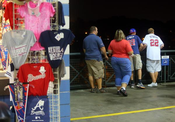 Baseball fans look over a railing at Turner Field near the scene where a man fell about 65 feet to his death Monday night.