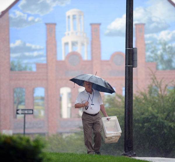 Lehigh County Courthouse mail services employee Ken Snyder of Allentown tries to stay dry while walking down Court Street behind Lehigh County Courthouse Tuesday morning. /// - ALLENTOWN - EMILY ROBSON / THE MORNING CALL - Taken Tuesday, August 13, 2013.