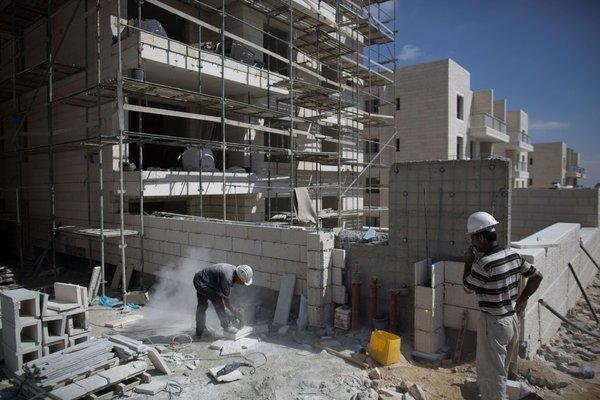 Builders work at a new housing project in the Jewish settlement of Gilo on Monday. The housing is being built on land annexed by Israel in 1967.