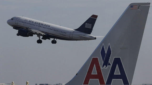 A U.S. Airways jet departs Washington's Reagan National Airport next to American Airlines jets in February.