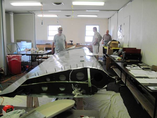 Volunteers work on a section of a wing of an airplane that will be used in mission work.