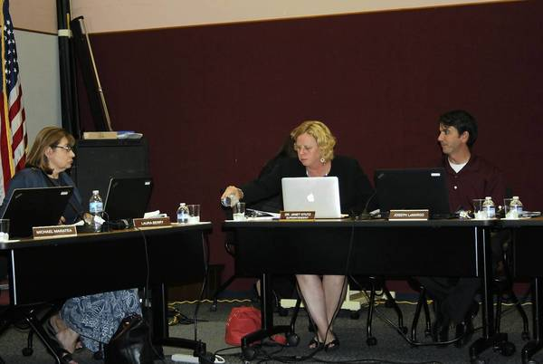 Orland School District 135 Superintendent Janet Stutz, center, fills her water glass while board member Laura Berry, left, and board President Joe La Margo talk prior to the Aug. 12 meeting of the District 135 board.