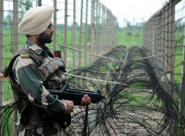 An Indian Border Security Force soldier patrols near the fence at the de facto border with Pakistan in the Kashmir region.