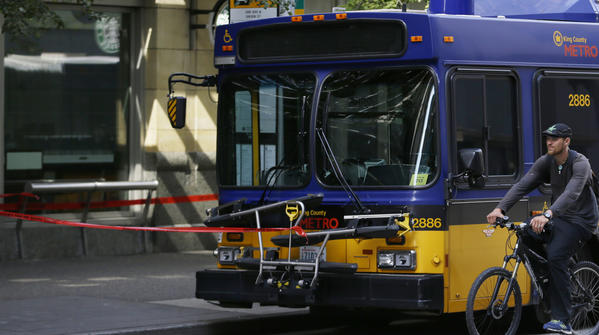 A cyclist rides past a bus in which the driver was shot by a gunman in downtown Seattle.