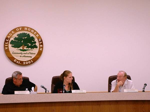 Homer Glen Plan Commission member Tom Bernicky, left, Homer Glen village staff liaison Erin Venard and commission member Don Mitchell discuss village business during an Aug. 5 commission meeting.