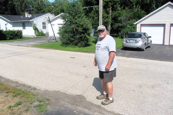 Bob Duprey, a resident of Lake Zurich's The Heights neighborhood, stands next to a pothole in front of his home. Lake Zurich officials had to push back the resurfacing of a number of village streets due to budget shortcomings.