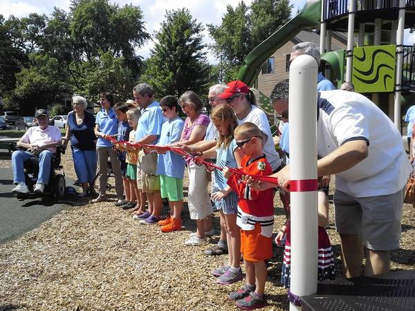 Residents prepare to cut the red ribbon on Aug. 10, officially reopening the revamped Crestwood Park near downtown Northbrook after a redesign added a new playground, tennis courts and fitness equipment.