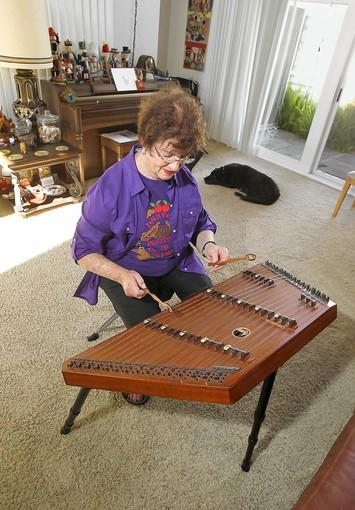 Barbara Gershman practices her hammered dulcimer, a table-like percussion string instrument, in her Huntington Beach home. She is vice president of the Southern California Dulcimer Heritage Group and has been at it 25 years.