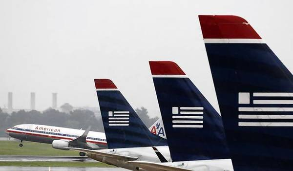 An American Airlines jet takes off while U.S. Airways jets are lined up at Reagan National Airport in Washington.