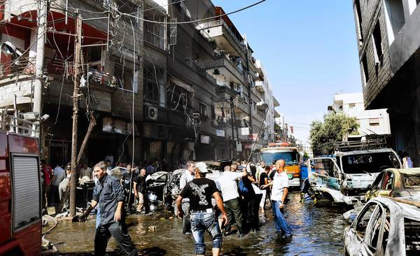 Residents gather at the scene of a car bombing in Jaramana, Syria, that left 10 people dead. Another blast hit the Damascus suburb 12 days later, killing 18.