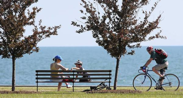 A woman and child rest on a bench as a bicyclist pedals past at the Lakefront Trail near 39th Street in June.