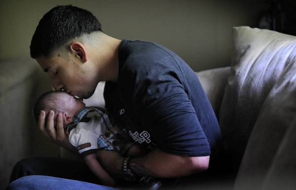 Former Marine Luis Garcia kisses his sleeping three-week-old son, Luis Andres, at their Zion home on Thursday.
