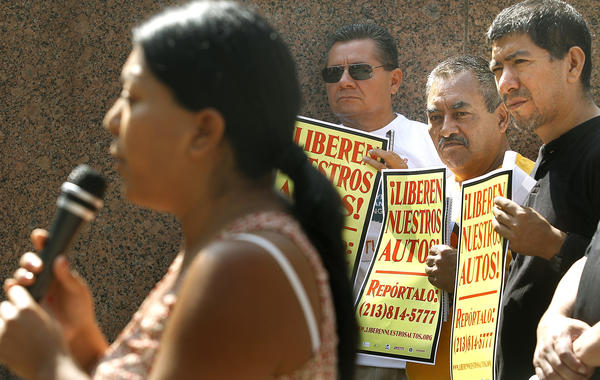 Maria Hernandez, left, gives her testimony on being stopped by the police and arrested for driving without a license, as Mario Fuentes, Jose Diaz, and Reyes Juarez, from left, look on during a press conference by the Free Our Cars Coalition.