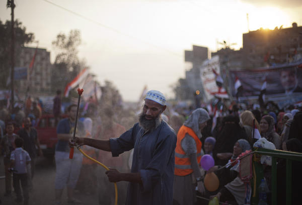 A supporter of Egypt's ousted president Mohammed Morsi sprays water on protesters outside Rabaa al Adawiya mosque in Cairo.