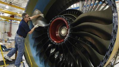 Empleado de Pratt & Whitney trabaja en el motor de un avion.