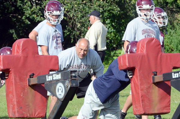 First-year Charlevoix High School varsity football coach Ron Bindi (middle) watches over practice Tuesday in Charlevoix. Bindi takes over a Rayder team which finished 1-8 last season after last season guiding Bellaire to the eight-man state championship