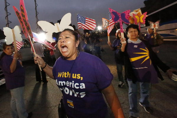 Maria Ortiz, who works as a janitor, shouts slogans at an immigration rally held at the Dodger Stadium parking lot before their departure to Bakersfield for a bigger rally later Wednesday.