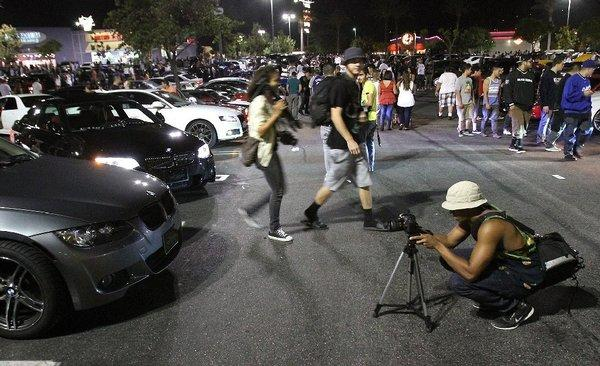 A photographer takes a picture of of a custom car at the Empire Center in Burbank on Tuesday night. The event forced police to close surrounding streets and turn away hundreds more cars.